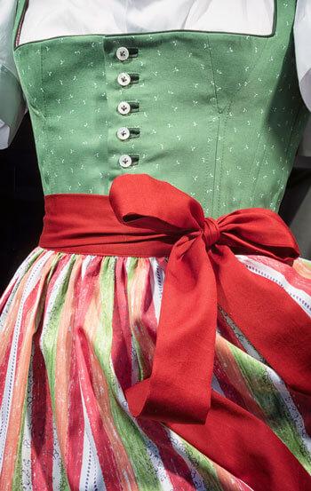 Rot-weiß-grüne Dirndlschürze mit Schleife auf grünem Dirndl