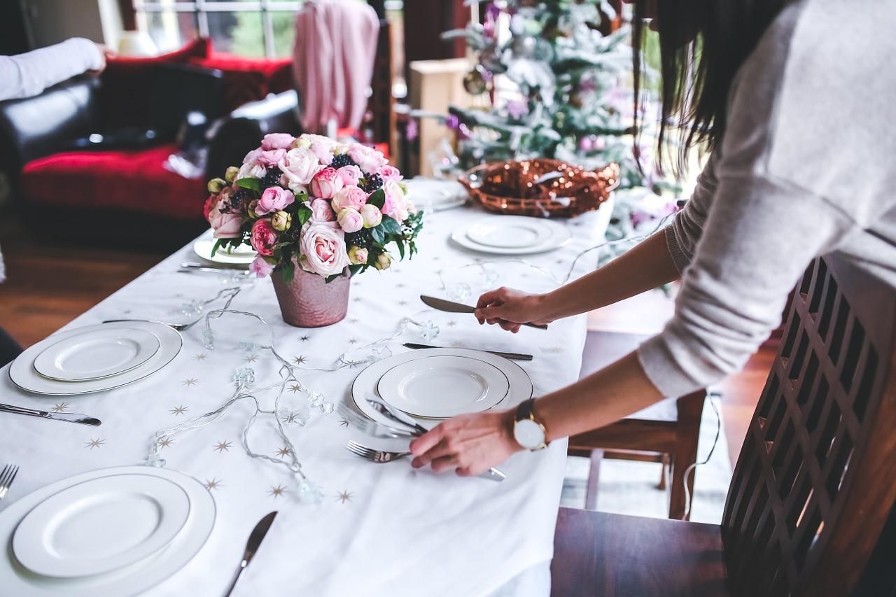 Frau deckt den Tisch mit Tellern, Tassen und Besteck