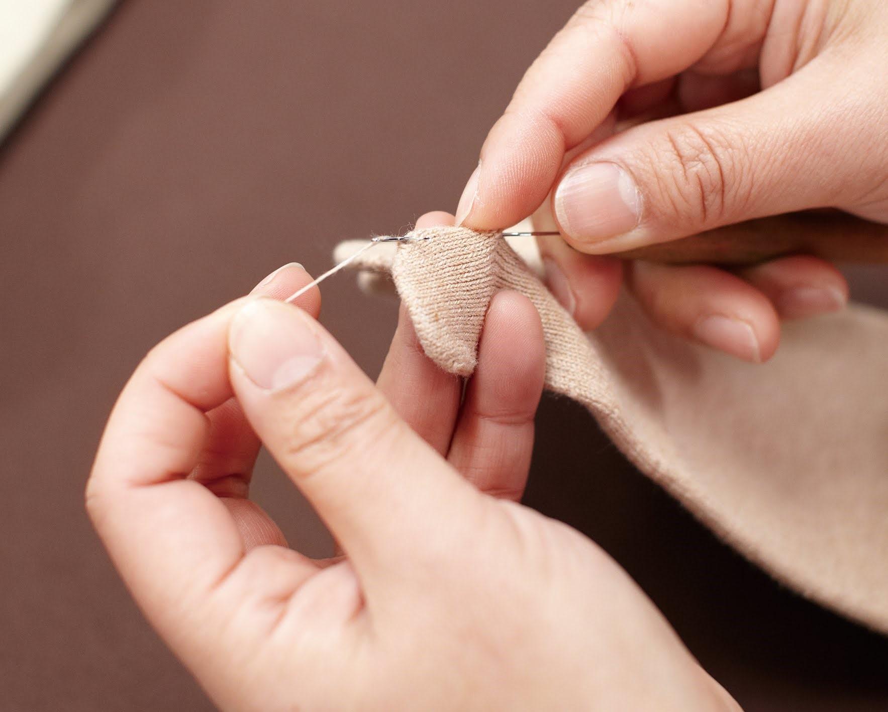 Ein Bild-Ausschnitt von zwei Händen, wie sie Loch ausgelöst durch einen losen Faden an der Zehenkammer einer Knitido Zehensocke stopfen.