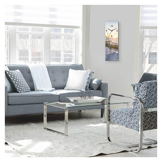 Wanduhr aus Glas im Hochformat mit Strand Motiv neben Sofa im Wohnzimmer von Artland im Onlineshop Artgalerie Bildershop