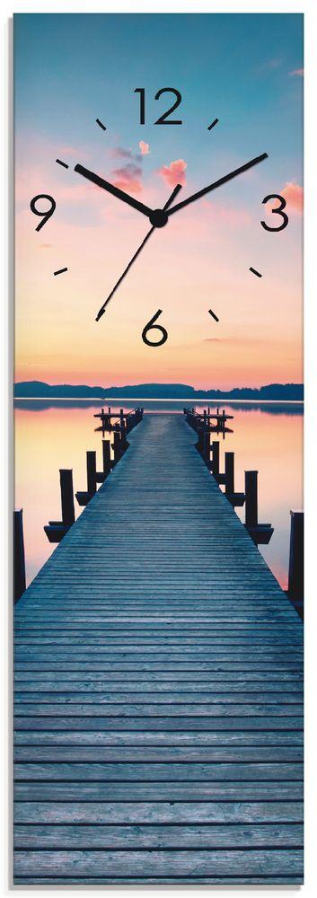 Jenny Sturm: Langer Pier am See im Sonnenaufgang - Wanduhr auf Glas