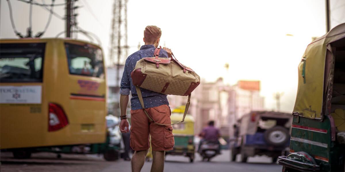 DRAKENSBERG Long Weekender Reisetasche Tragebeispiel geschulter in Neu Delhi als Fußgänger mitten im Verkehr